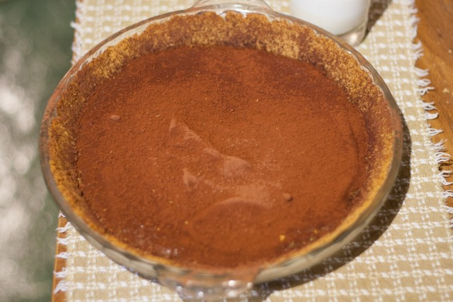 A chocolate pie in a glass pie plate with a graham-cracker crust and cocoa powder on top