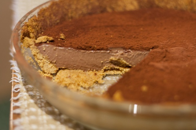 A chocolate pie with one slice remove; the photo is taken close to the horizontal to display the texture of the filling and the profile of the crust.