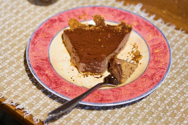 A slice of chocolate pie on a dessert plate with one bite of pie loaded on a fork.
