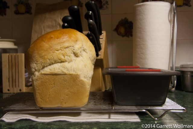 Photo showing a loaf of Tessinerbrot on a cooling rack side by side with the loaf pan