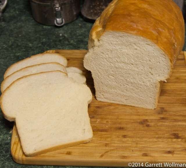 Photo showing three slices of Tessinerbrot on a cutting board next to the rest of the loaf (uncut)