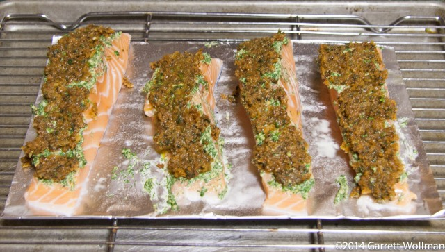 Photo shows four salmon fillets on an oiled piece of aluminum foil, which in turn sits on a wire rack set inside a half-sheet pan.