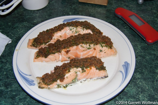 Photo shows three cooked herb-crusted salmon fillets on a white plate with blue decoration. The salmon is light orange in color; the top is covered with green chopped herbs, which are in turn covered with browned bread crumbs. A food thermometer sits on the counter next to the plate.