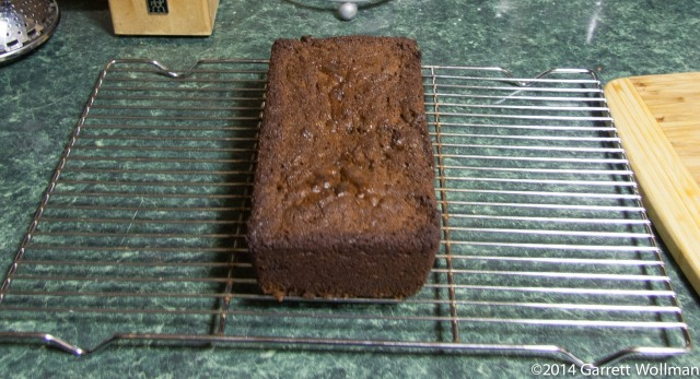 Photo showing a loaf of gingerbread sittiing on a wire cooling rack