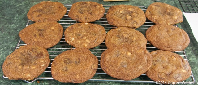 Photo showing twelve chocolate-chip cookies on a wire cooling rack
