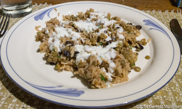 A serving of the finished rice-and-lentil dish, with yogurt sauce, on a dinner plate