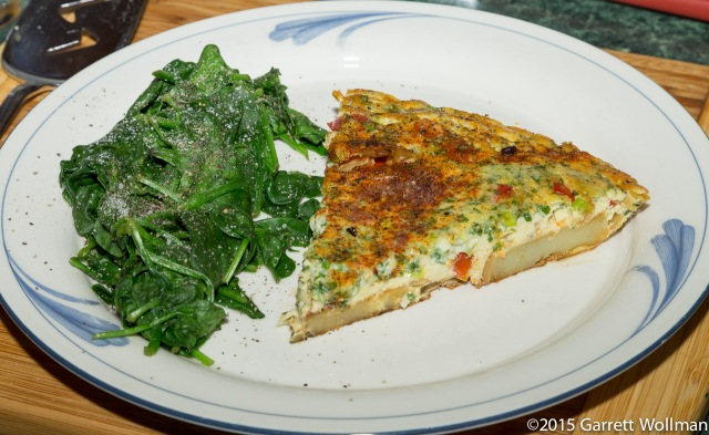Tortilla slice on a plate with some steamed spinach