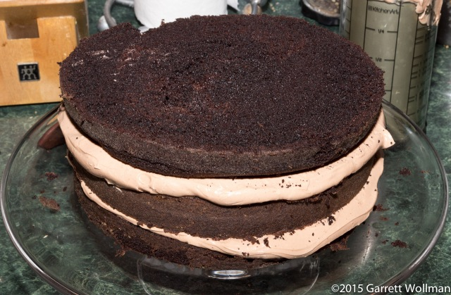 All three layers of cake on a stand, with filling