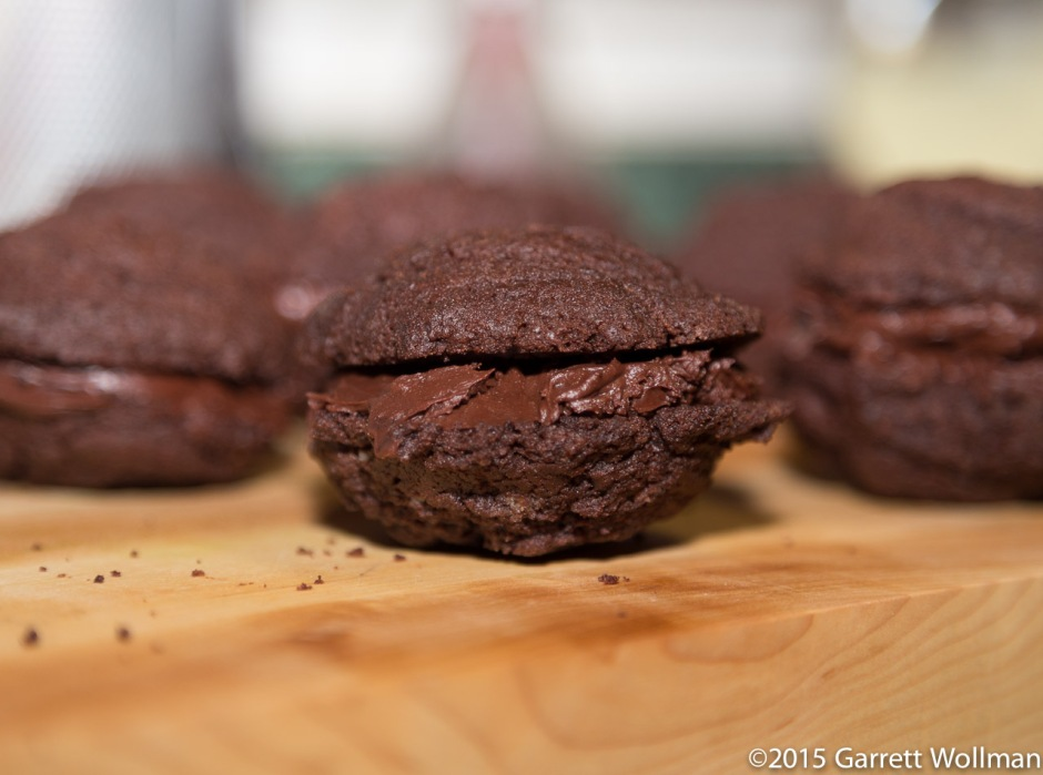 Lots of whoopie pies shown edge-on, resting on a wooden chopping block, taken with a very wide aperture so that only one is in focus