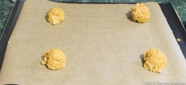 Four small portions of dough on a cookie sheet
