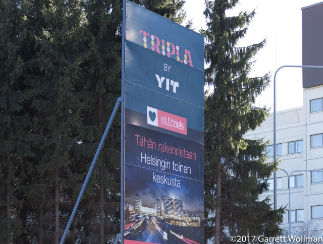 Photo shows a tall roadside sign advertising a new development