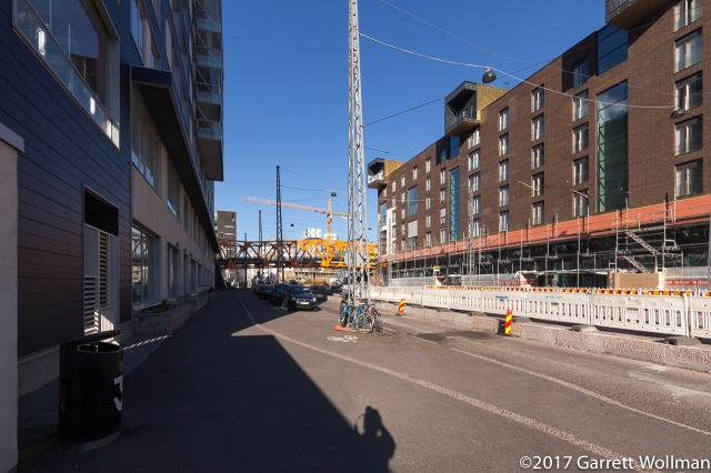 Pedestrian bridge (yellow) across Välimerenkatu, with cranes and the Clarion in the distance
